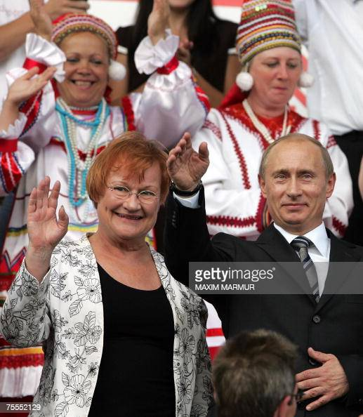Russian President Vladimir Putin and Finland's President Tarja Halonen wave as they attend the opening ceremony of an ethnic festival in Saransk some...