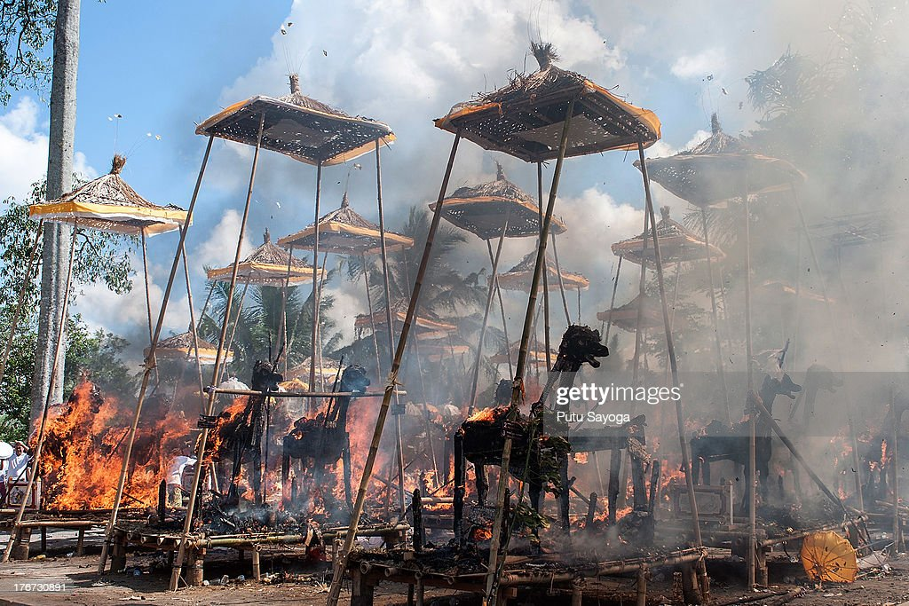 Sarcophagi burn at the cremation site during a Balinese Hindu mass cremation on August 18, 2013 in Ubud, Bali, Indonesia. More than 60 corpses were collectively cremated to share the expense of the ceremony. Well known as Ngaben, it is one of the most important ceremonies for Balinese Hindu people, as they believe it will free the spirit from the deceased body so it can reincarnate.