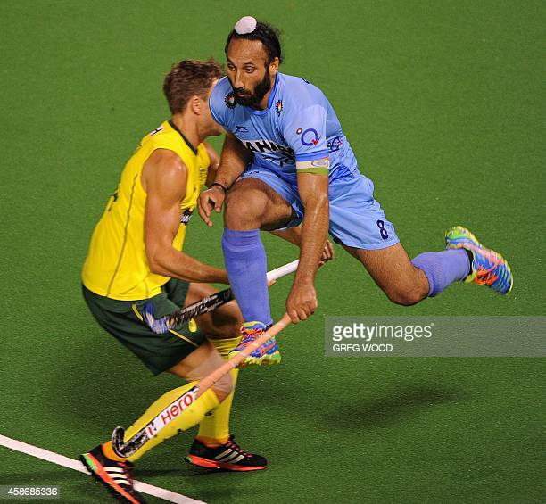 Sardar Singh from India jumps high alongside Nicholas Budgeon from Australia during the final match of the four match field hockey Test series in...