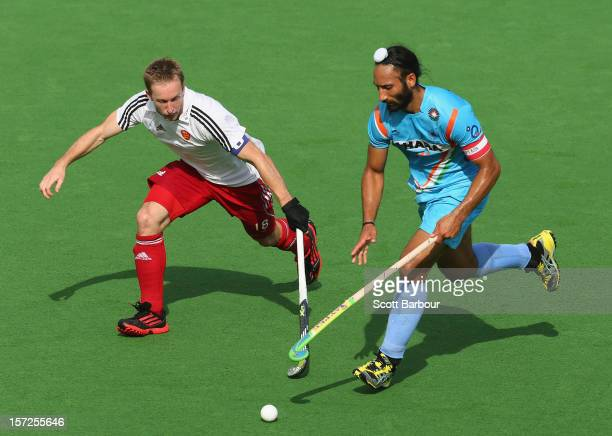 Sardar Singh of India and Barry Middleton of England compete for the ball during the match between England and India on day one of the Champions...