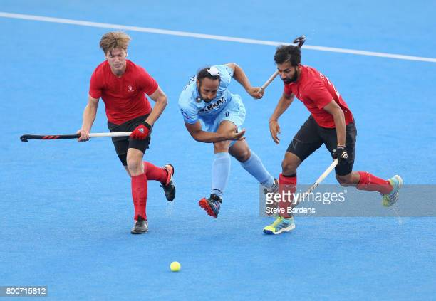 Sardar Singh of India battles for possession with Foris Van Son of Canada and Sukhi Panesar of Canada during the 5th/6th place match between India...