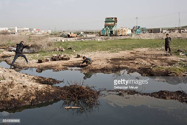 Sardesht Ezidiar and Jamal play in polluted water near the banks of the Tanjero river The family of Yezidis displaced from Sinjar live next to an oil...
