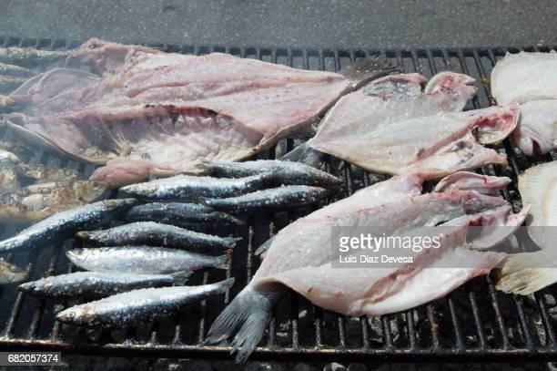 Sardines and sea basses roasting On Barbeque Grill