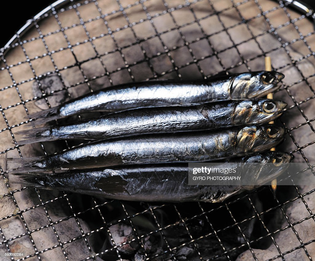 Sardines cooking on charcoal brazier
