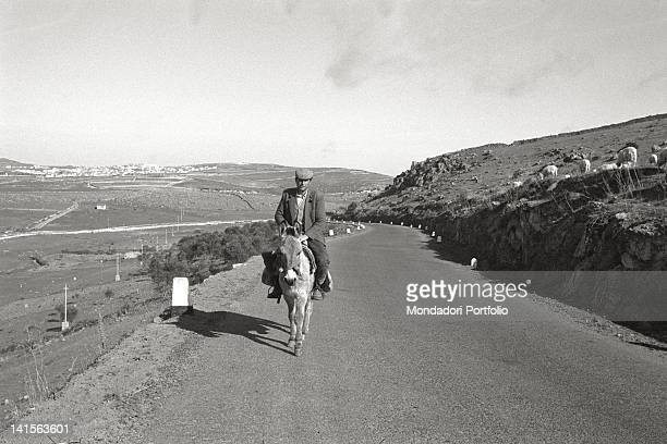 A Sardinian shepherd is running along a road in the hills of Barbagia in the province of Nuoro on a donkeyback March 1967