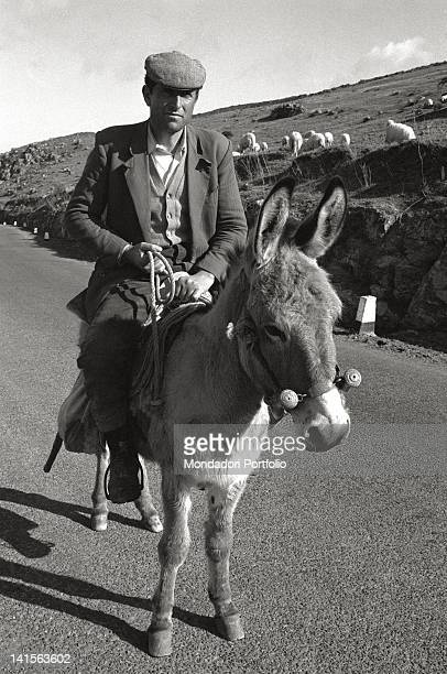 A Sardinian shepherd is running on a donkeyback along a road on the hills of Barbagia in the province of Nuoro March 1967