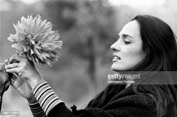Sardinian singer Maria Carta is shot in profile beside a big beautiful flower Rome 1974