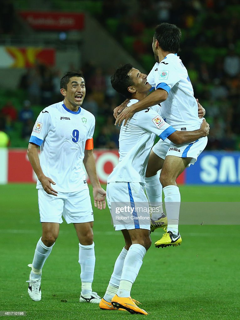 Sardor Rashidov of Uzbekistan celebrates with Jasur Khasanov and Odil Akhmedov after he scored a goal during the 2015 Asian Cup match between...