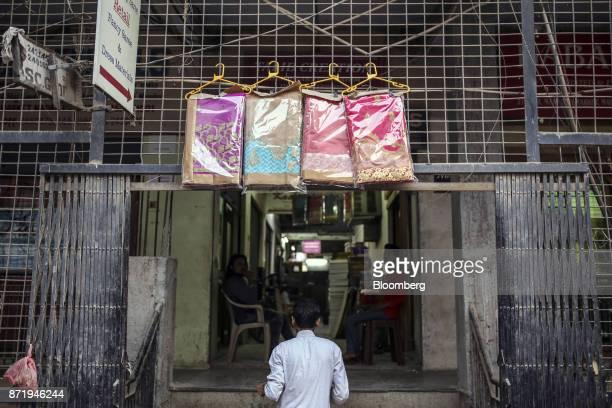 Sarees wrapped in plastic hang on display outside a saree store in Varanasi Uttar Pradesh India on Saturday Oct 28 2017 In Varanasi where the...