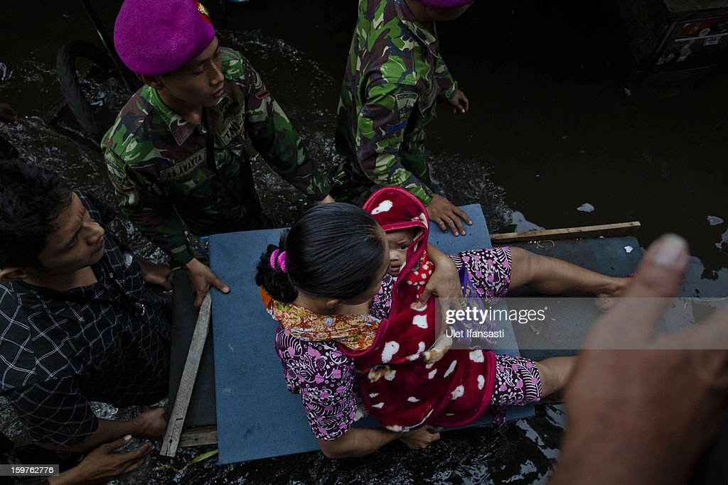 Sarianty holds her daughter Mutiara Rahmadani as they are evacuated by Indonesian Armyas major floods hit North Jakarta on January 20, 2013 in Jakarta, Indonesia. The death toll has risen to at least 21since severe flooding struck the city on January 17. The US has offrered US$150,000 (Rp 1.44 billion) in aid.