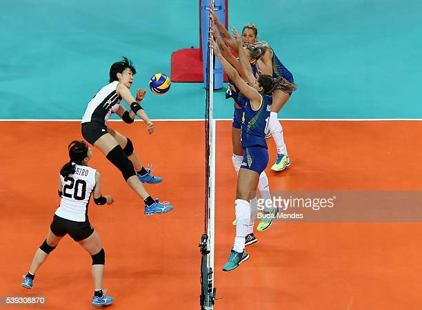 Sarina Koga of Japan spikes the ball as Thaisa Menezes and Natalia Pereira of Brazil defend during the match between Brazil and Japan on day 2 the...