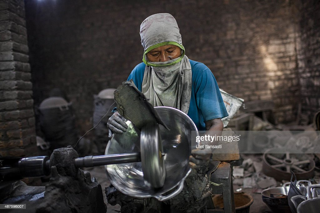 Sarono, a worker polishes a pan at Putra Logam workshop on May 1, 2014 in Yogyakarta, Indonesia. The pan polishers are paid around Rp. 40.000 (USD 3.46) per day. Today is International Labour Day, which aims to bring attention to working conditions, higher wages, and working hours across the world. Protesters across Indonesia have organised rallies to demand higher wages, as Indonesia recognises its first national labour day holiday.