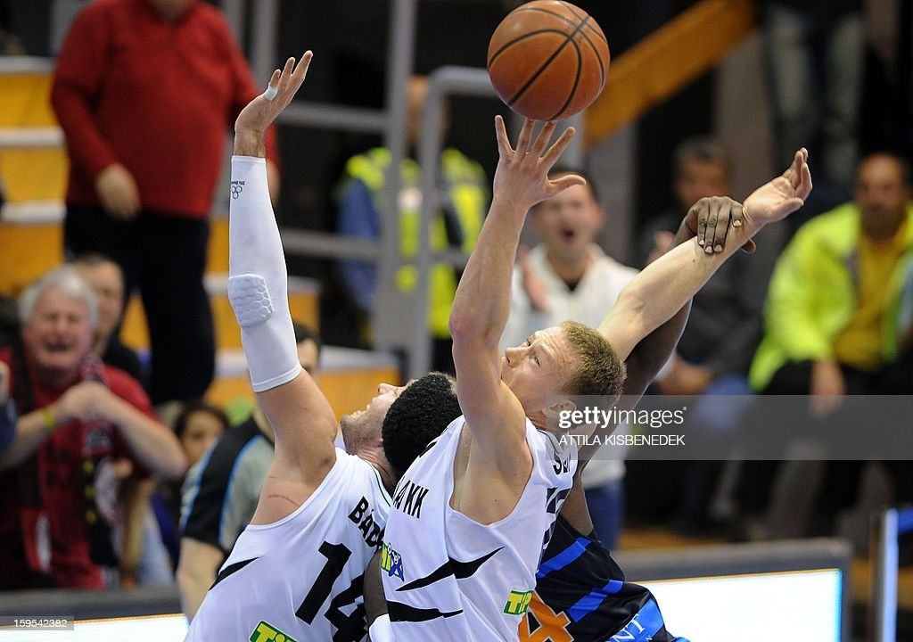 Sarra Camara (L) and Ludovic Vaty (R) of Hungarian KK Szolnoki Olaj fights for the ball with Juan Edwards (covered) of French BCM Gravelines Dunkerque in the locak sport hall on January 15, 2015 during their FIBA EuroChallenge match.