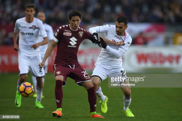Sasa Lukic of FC Torino is challenged by Bruno Henrique Corsini of US Citta di Palermo during the Serie A match between FC Torino and US Citta di...
