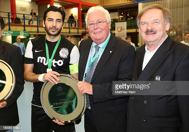 Sascha Enrico de la Cuesta Seco of Hamburg and members of the DFB pose with the cup after the DFB Futsal Cup final match between Hamburg Panthers and...