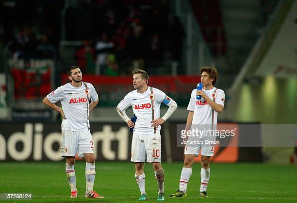 Sascha Moelders Daniel Baier ad JaCheol Koo of Augsburg look dejected after the Bundesliga match between FC Augsburg and SC Freiburg at SGL Arena on...