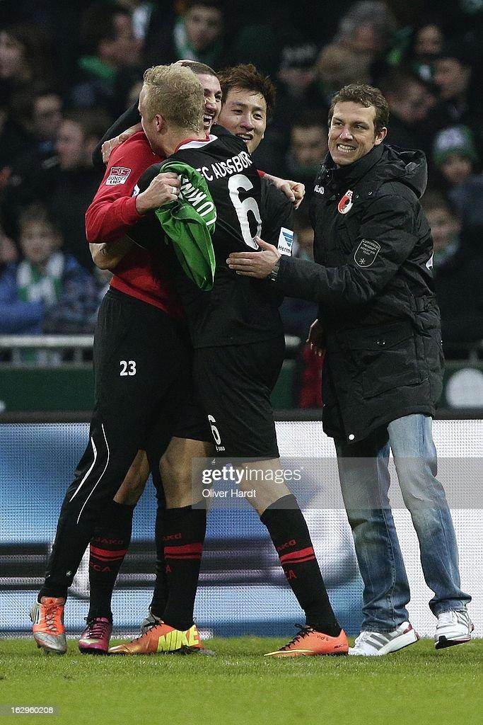 Sascha Moelders (L), Kevin Vogt (C) and Head coach Markus Weinzierl (R) of Augsburg celebrate after the Bundesliga match between SV Werder Bremen and FC Augsburg at Weser Stadium on March 2, 2013 in Bremen, Germany.