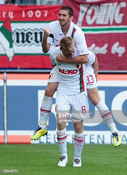 Sascha Moelders of Augsburg celebrates with team mate Axel Bellinghausen after scoring his team's first goal during the Bundesliga match between FC...