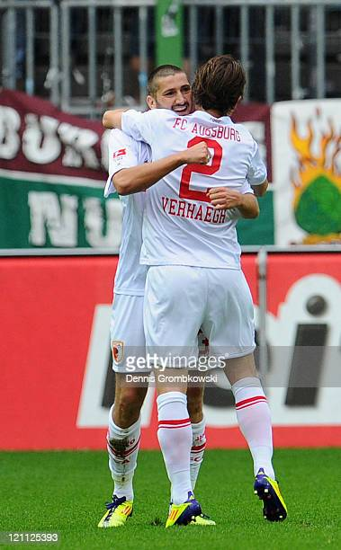 Sascha Moelders of Augsburg celebrates with team mate Paul Verhaegh after scoring his team´s opening goal during the Bundesliga match between 1 FC...