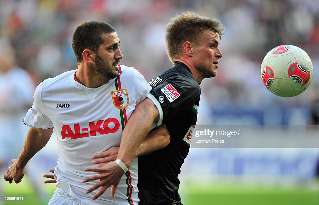 Sascha Moelders (L) of Augsburg challenges Florian Trinks of Fuerth during the Bundesliga match between FC Augsburg and SpVgg Greuther Fuerth at SGL Arena on May 18, 2013 in Augsburg, Germany.