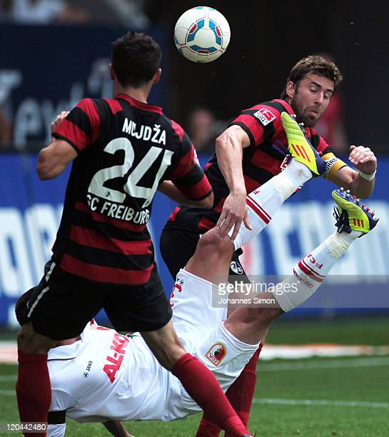 Sascha Moelders of Augsburg fights for the ball with Mensur Mujdza and Heiko Butscher of Freiburg during the Bundesliga match between FC Augsburg and...