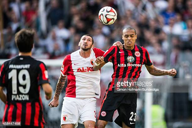 Sascha Moelders of Augsburg jumps for a header with Bamba Anderson of Frankfurt during the Bundesliga match between Eintracht Frankfurt and FC...