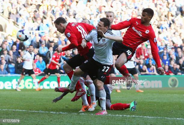 Sascha Riether of Fulham scores an own goal for Cardiff City's third as he is challenged by Jordon Mutch and Fraizer Campbell of Cardiff City during...