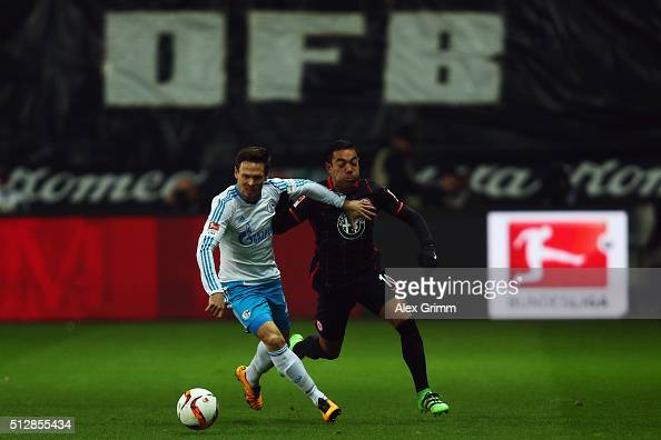 Sascha Riether of Schalke is challenged by Marco Fabian of Frankfurt during the Bundesliga match between Eintracht Frankfurt and FC Schalke 04 at...
