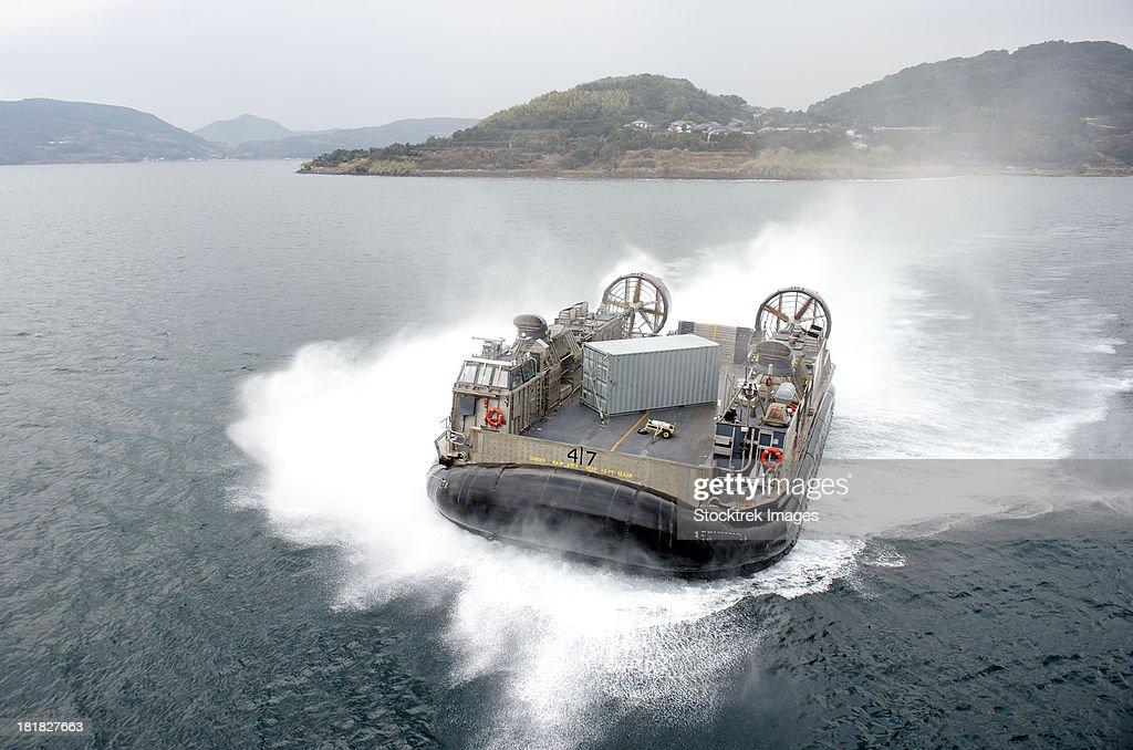 Sasebo, Japan, January 24, 2013 - A landing craft air cushion (LCAC) approaches the stern gate of the amphibious assault ship USS Bonhomme Richard.