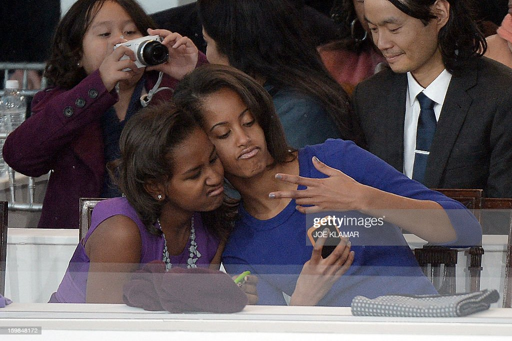 Sasha and Malia Obama daughters of US President Barack Obama take a photo of themselves during the Presidential Inaugural Parade on January 21 2013...