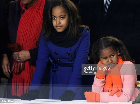 Sasha and Malia Obama watch the Inaugural Parade from the reviewing stand in front of The White House January 20 2009 in Washington DC Obama was...