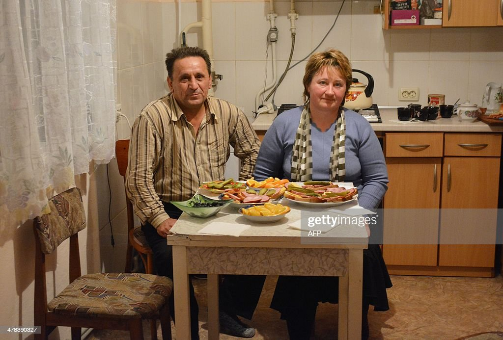 Sasha (2nd L) and Olga Onoprienko sit at the dinner table in their home in Gzhankoy, Crimea, on March 11, 2013. The Onoprienko family is split down the middle on whether Crimea should become part of Russia or stay with Ukraine, reflecting deep divisions between even blood relatives ahead of the March 16 referendum on the region's future. Dima, 17 - one of the family's sons - is a computing student who loves the Beatles, 'Breaking Bad' and Western sportswear -- and he and his mother Olga, a kindergarten teacher, are both desperate for Crimea to remain an autonomous region of Ukraine. But Dima's bodybuilding brother Zhenya, 20, and taxi driver father Sasha believe that only closer ties with President Vladimir Putin's Russia can bring Crimea the jobs and stability it desperately needs. AFP PHOTO / KATHERINE HADDON