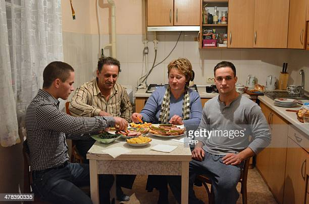 Sasha and Olga Onoprienko sit at the dinner table with their sons Dima and Genya in their home in Gzhankoy Crimea on March 11 2013 The Onoprienko...