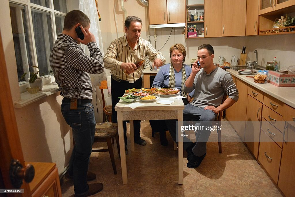 Sasha (2nd L) and Olga Onoprienko sit at the dinner table with their sons Dima (L) and Genya, in their home in Gzhankoy, Crimea, on March 11, 2013. The Onoprienko family is split down the middle on whether Crimea should become part of Russia or stay with Ukraine, reflecting deep divisions between even blood relatives ahead of the March 16 referendum on the region's future. Dima, 17 -- a computing student who loves the Beatles, 'Breaking Bad' and Western sportswear -- and his mother Olga, a kindergarten teacher, are both desperate for Crimea to remain an autonomous region of Ukraine. But Dima's bodybuilding brother Zhenya, 20, and taxi driver father Sasha believe that only closer ties with President Vladimir Putin's Russia can bring Crimea the jobs and stability it desperately needs.