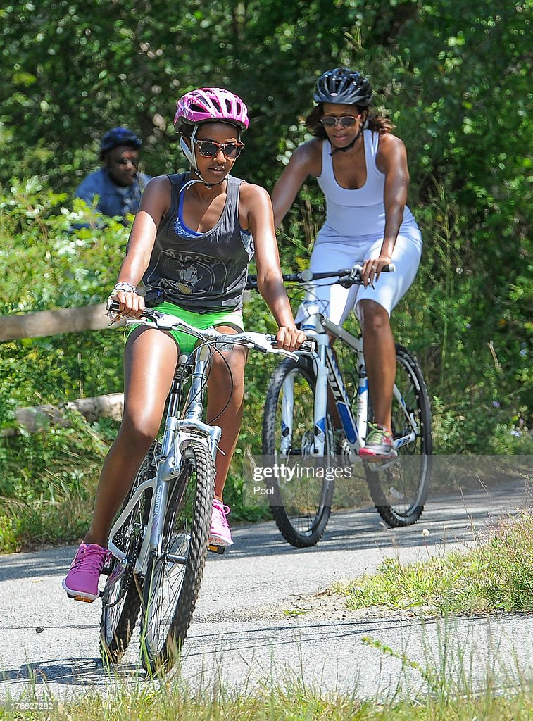 Sasha Obama (C) and first lady Michelle Obama (R) ride bikes during a vacation on Martha's Vineyard August 16, 2013in West Tisbury, Massachusetts. Obama and his family are on a weeklong vacation.