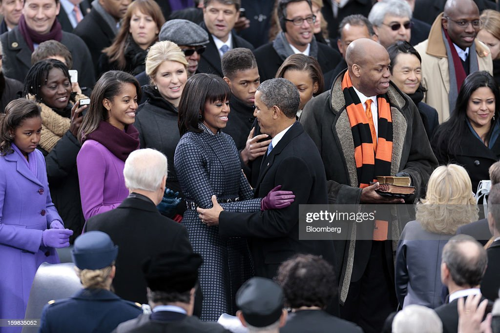 Sasha Obama, left and Malia Obama, second from left, watch as first lady Michelle Obama and U.S. President Barack Obama embrace at the Capitol during the U.S. presidential inauguration in Washington, D.C., U.S., on Monday, Jan. 21, 2013. Michelle Obama's brother Craig Robinson, second from right, and President Obama's sister Maya Soetoro-Ng, right, stand next Obama. As he enters his second term, President Barack Obama has shed the aura of a hopeful consensus builder determined to break partisan gridlock and adopted a more confrontational stance with Republicans. Photographer: Andrew Harrer/Bloomberg via Getty Images