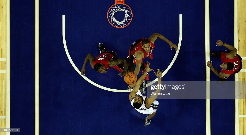 Sasha Vujacic #20 of the Nets jumps against Alexis Ajinca #42 and Ed Davis #32 of the Raptors during the NBA match between New Jersey Nets and the Toronto Raptors at the O2 Arena on March 4, 2011 in London, England.