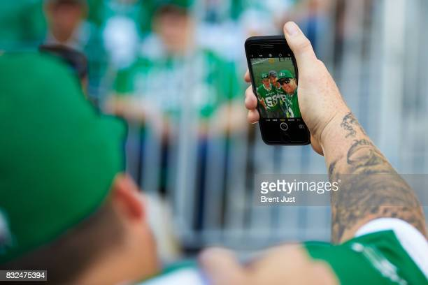 Saskatchewan Roughrider fans take a selfie on the field before the game between the BC Lions and the Saskatchewan Roughriders at Mosaic Stadium on...