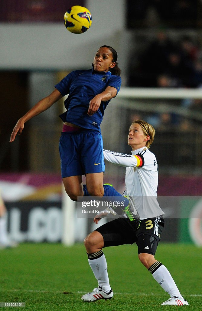 Saskia Bartusiak of Germany (R) jumps for a header with Marie Laure Delie of France during the international friendly match between France and Germany at Stade de la Meinau on February 13, 2013 in Strasbourg, France.