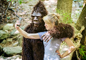"""A young woman takes a """"selfie"""" self-portrait with Sasquatch/Bigfoot in the wilderness."""