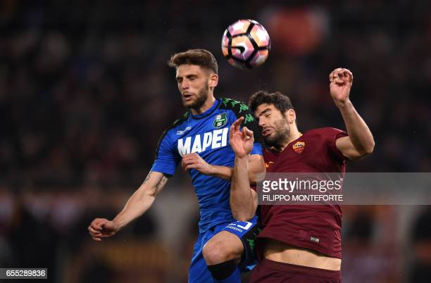 TOPSHOT Sassuolo's forward Domenico Berardi and Roma's Argentinian defender Federico Fazio go for a header during the italian Serie A football match...