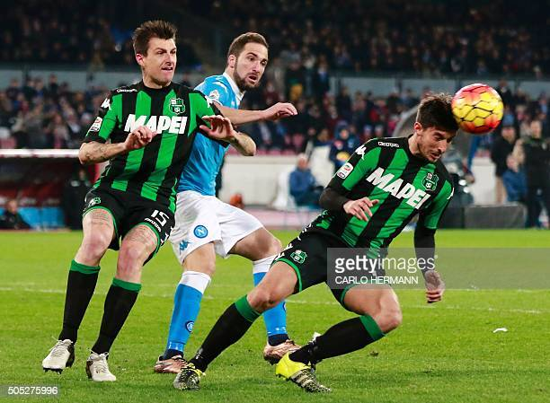Sassuolo's Italian defender Federico Peluso heads the ball eyed by Napoli's ArgentinianFrench forward Gonzalo Higuain and teammate Italian defender...
