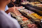Kuala Lumpur, Malaysia: People talk about Satay skewers in Chinatown at night.