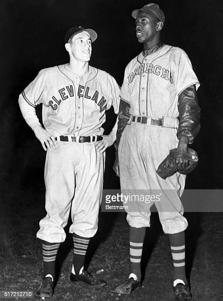 Satchel Paige of the Kansas City Monarchs a Negro league team stands with Bob Feller of the Cleveland Indians The two men led teams of black and...