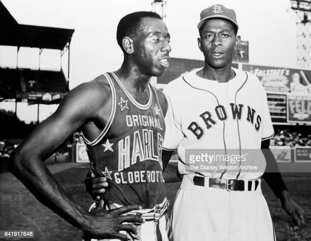 Satchel Paige pitcher of the St Louis Browns and Goose Tatum of the Harlem Globetrotters former teammates in Negro League Baseball catch up on old...
