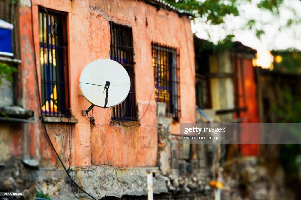Satellite Dish Attached to Side of Old Building