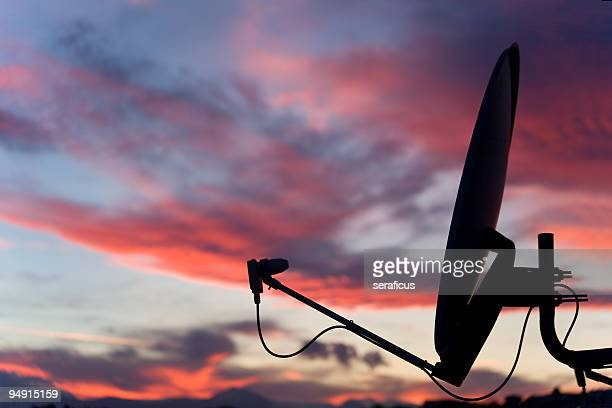 A satellite dish in front of a sunset sky