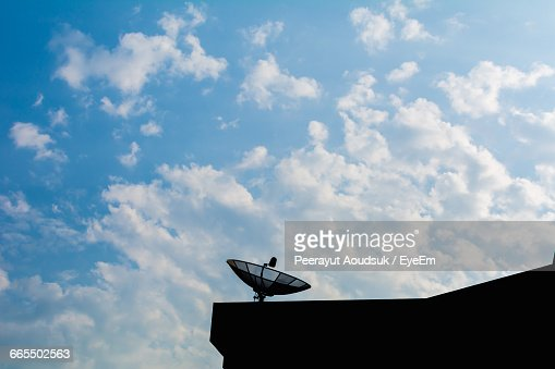 Satellite Dish On Silhouette Building Against Sky