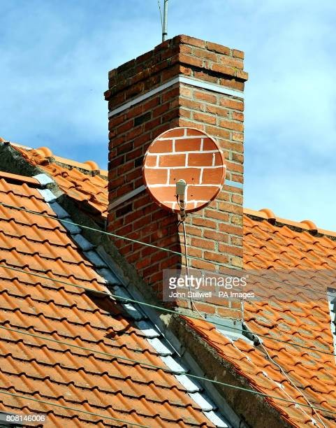 A satellite dish painted to blend in with the surrounding brickwork and tiles on the roof of a house in Fromelles northern France