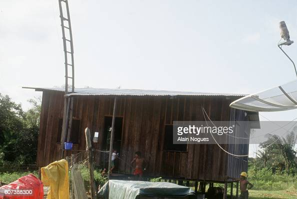 A satellite dish sits alongside a family's hut in the South American rainforest With the aid of a satellite dish the Brazilian family living in...